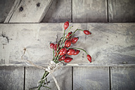 Bouquet of rose hips on wooden board, close-up - SBDF000337