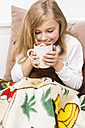 Little girl holding cup of hot chocolate, studio shot - STB000160
