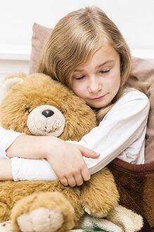 Sad little girl cuddling with her teddy bear, studio shot - STB000162