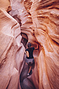 USA, Utah, Escalante, Peek-A-Boo and Spooky Slot Canyons, young woman climbing in gorge - MBEF000838