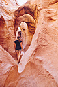 USA, Utah, Escalante, Peek-A-Boo and Spooky Slot Canyons, young woman looking at the beauty of nature - MBEF000826