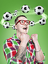 Young man with flying footballs around his head, Composite - STKF000506