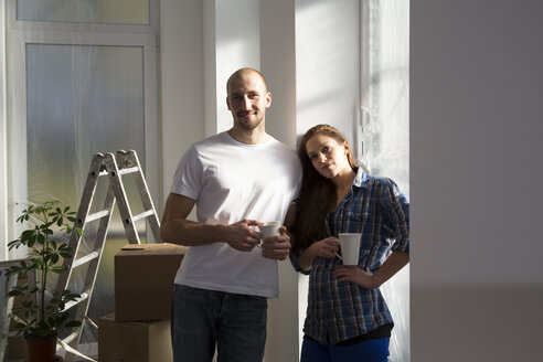 Young couple moving into new home, taking a coffee break - FKF000309
