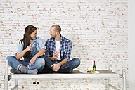 Young couple moving into new home, drinking champagne - FKF000337