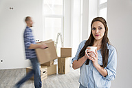 Young couple moving into new home, woman holding cup of coffee - FKF000339