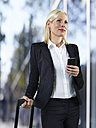 Portrait of business woman with luggage and smart phone - STKF000530