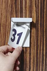 Hand tearing off calendar sheet of  December 31st - STKF000621