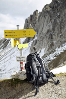 Austria, Tyrol, Karwendel mountains, Rucksack under sign post - TKF000174