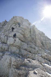 Austria, Tyrol, Karwendel mountains, Mountaineers climbing rockface - TKF000188