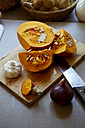 Germany, Hokkaido pumpkin on chopping board - TKF000191