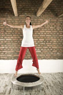 Germany, Bavaria, Woman jumping on trampoline - RNF001293