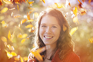 Portrait of happy young woman with swirling autumn leaves around her, close-up - BGF000006