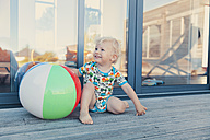 Little boy sitting besides a beach ball - MFF000679