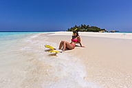 Maledives, young woman sitting at beach - AMF001225