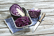Red cabbage, kitchen knife and kitchen towel on wooden table - MAEF007341