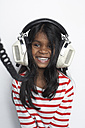 Portrait of smiling girl hearing music with headphones - FSF000307