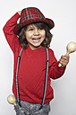 Portrait of smiling little boy with wooden rattle wearing hat and suspenders - FSF000314