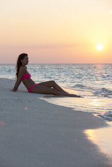 Maledives, young woman sitting at beach - AMF001244