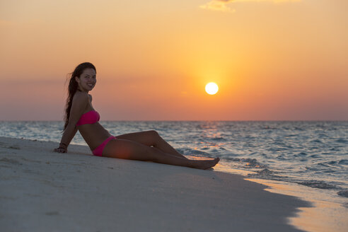 Maledives, young woman sitting at beach - AMF001245