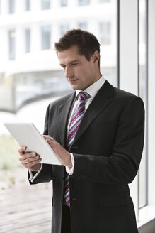 Poland, Warzawa, young businessman using tablet computer - MLF000341