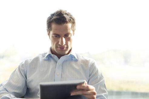 Poland, Warzawa, businessman using tablet computer at hotel lounge - MLF000365