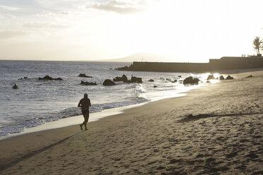 Spain, Lanzarote, Puerto del Carmen, Man jogging at beach - JAT000473