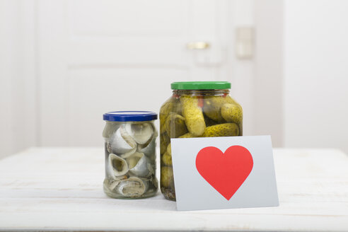 Glass of pickled cucumbers, a glass of rollmops and a postcard with red heart on white wooden table - DRF000281