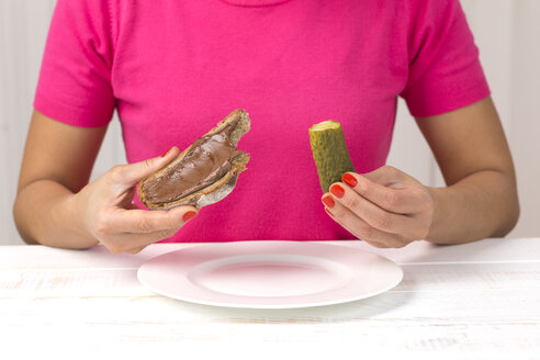 Young woman eating pickled cucumber and slice of bread with chocolate cream - DRF000286