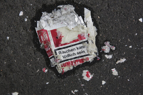 Squashed cigarette packet lying on the street, close-up - JAT000507