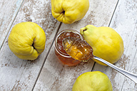 Four quinces (Cydonia oblonga), a spoon  and a glass of quince marmalade on wooden table - CSF020330