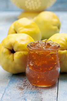 Four quinces (Cydonia oblonga), a spoon and a glass of quince marmalade on wooden table - CSF020322