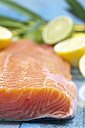 Salmon fillet (Salmo salar) and sliced lemons on blue wooden table - CSF020336