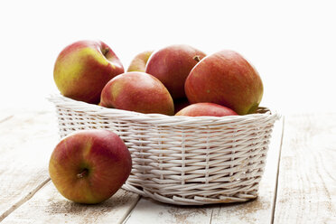 Apples (Malus) in white basket on wooden table - CSF020345