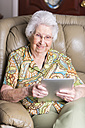 Smiling aged woman looking at tablet computer - ABAF001067