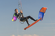 Germany, Baden-Wuerttemberg, Fischbach, Kitesurfer mid-air above Lake Constance - SH001030