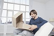 Germany, Munich, Man unpacking cardboard box - RBF001473