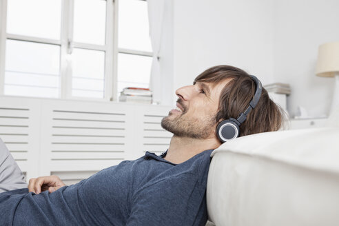 Germany, Munich, Man sitting on sofa, wearing head phones - RBF001482