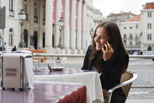 Portugal, Lisboa, Baixa, Rossio, Praca Dom Pedro IV, Teatro Nacional, young woman telephoning at street cafe - BIF000046