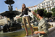Portugal, Lisboa, Baixa, Rossio, Praca Dom Pedro IV, young woman balancing on the rim of a fountain - BIF000040
