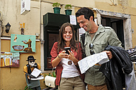 Portugal, Lisboa, Carmo, Calcada du Duque, young couple with city map and smart phone trying to orientate - BIF000058