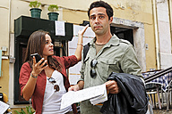 Portugal, Lisboa, Carmo, Calcada du Duque, young couple with city map and smart phone trying to orientate - BIF000059
