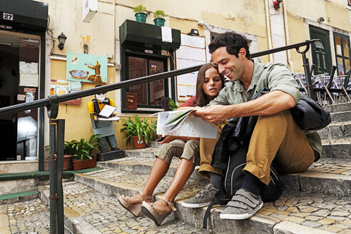 Portugal, Lisboa, Carmo, Calcada du Duque, young couple with city map sitting at stairs - BIF000060