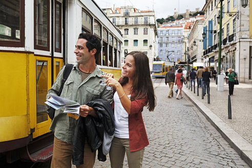 Portugal, Lisboa, Baixa, Rossio, young couple with city map in front of tram - BIF000065