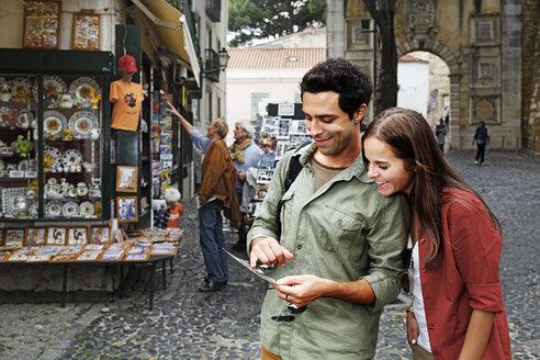 Portugal, Lisboa, Baixa, Rossio, young couple looking at postcard - BI000023