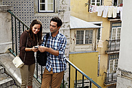 Portugal, Lisboa, Mouraria, young couple with smart phone standing at stairs - BIF000068