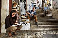 Portugal, Lisboa, Baixa, Rua do Madalena, young couple in front of antiquarian bookshop - BI000019