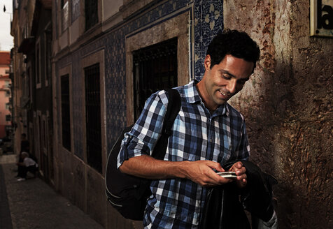 Portugal, Lisboa, Bairro Alto, young man looking at his mobile phone - BIF000069