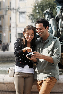 Portugal, Lisboa, Baixa, Rossio, Praca Dom Pedro IV, smiling young couple looking at own pictures - BIF000071