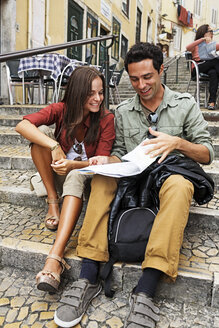 Portugal, Lisboa, Carmo, Calcada du Duque, young couple with city map sitting at stairs - BI000008