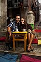 Portugal, Lisboa, Bairro Alto, young couple sitting at street cafe at dusk - BIF000003